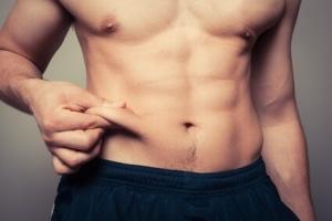 Ein trainierter Mann hält seine Bauchfalte in der Hand.